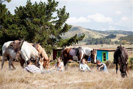 Horse riders taking break on grass, Pakiri Beach, Auckland, New Zealand Stock Photo - Premium Royalty-Free, Code: 614-07911671