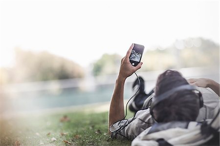 Young man lying on grass in park selecting music on smartphone Stock Photo - Premium Royalty-Free, Code: 614-07911687