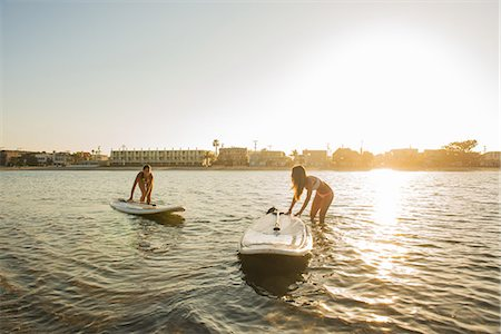 Two women pushing paddleboards at sunset, Mission Bay, San Diego, California, USA Stock Photo - Premium Royalty-Free, Code: 614-07911744