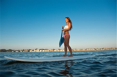 Young woman stand up paddleboarding, Mission Bay, San Diego, California, USA Stock Photo - Premium Royalty-Free, Code: 614-07911740