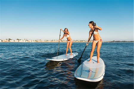 Two women chatting whilst stand up paddleboarding, Mission Bay, San Diego, California, USA Stock Photo - Premium Royalty-Free, Code: 614-07911741