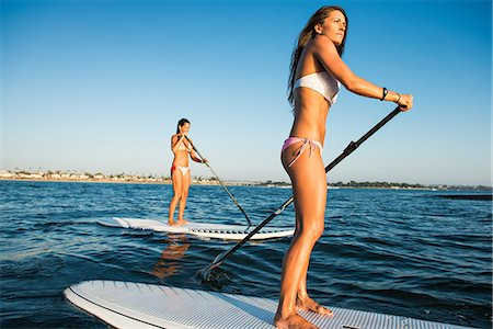 Two women stand up paddleboarding, Mission Bay, San Diego, California, USA Stock Photo - Premium Royalty-Free, Code: 614-07911742
