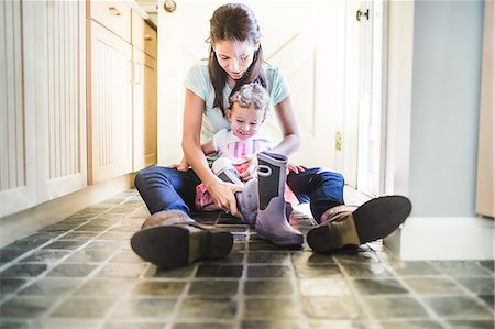 Mother and daughter putting on boots in kitchen Stock Photo - Premium Royalty-Free, Code: 614-07911847