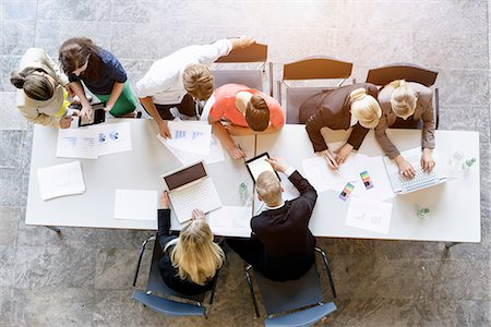 Overhead view of business team brainstorming at desk in office Stock Photo - Premium Royalty-Free, Code: 614-07911914