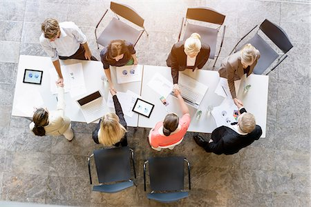 Overhead view of business team meeting clients at desk in office Stock Photo - Premium Royalty-Free, Code: 614-07911916