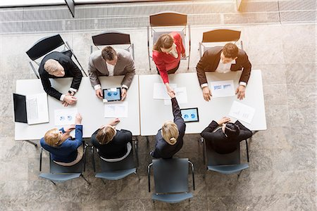 Overhead view of business team shaking hands with client at desk in office Stock Photo - Premium Royalty-Free, Code: 614-07911925