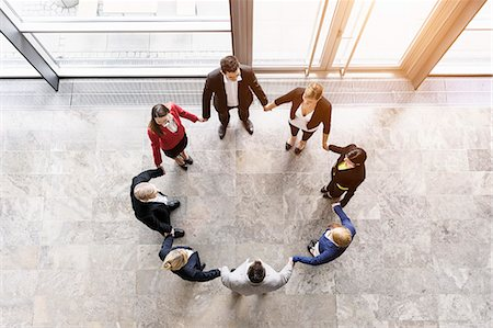 Overhead view of businessmen and women in circle holding hands Stock Photo - Premium Royalty-Free, Code: 614-07911922