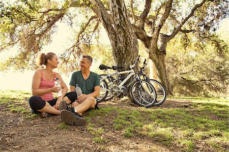 Mature cyclist couple taking a water break in park Stock Photo - Premium Royalty-Free, Code: 614-07911944