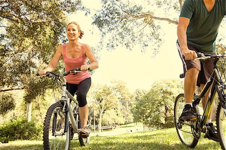 Mature couple cycling through park Stock Photo - Premium Royalty-Free, Code: 614-07911945