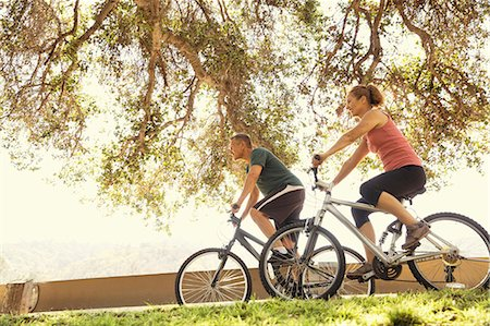 Mature couple cycling in park Stock Photo - Premium Royalty-Free, Code: 614-07911943