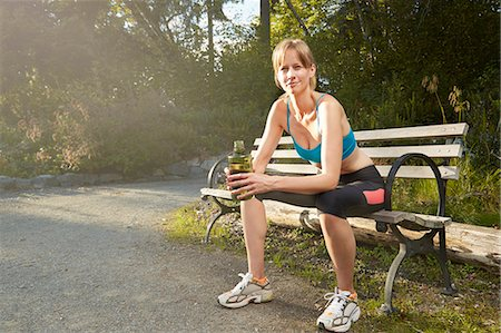 Portrait of smiling female runner taking a break on park bench Stock Photo - Premium Royalty-Free, Code: 614-07911963