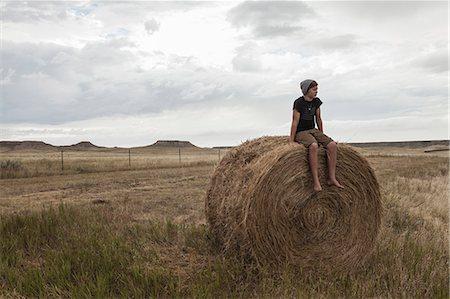 Teenage boy sitting on haystack in field, South Dakota, USA Stock Photo - Premium Royalty-Free, Code: 614-07912004