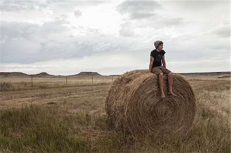 Teenage boy sitting on haystack in field, South Dakota, USA Stock Photo - Premium Royalty-Free, Code: 614-07912004