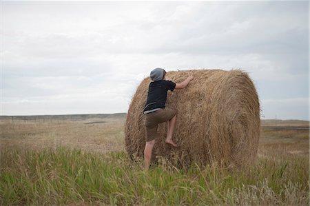 Teenage boy climbing on haystack, South Dakota, USA Stock Photo - Premium Royalty-Free, Code: 614-07912002