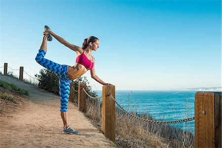 stretching (people exercising) - Young woman doing stretches on path by sea Stock Photo - Premium Royalty-Free, Code: 614-07912033