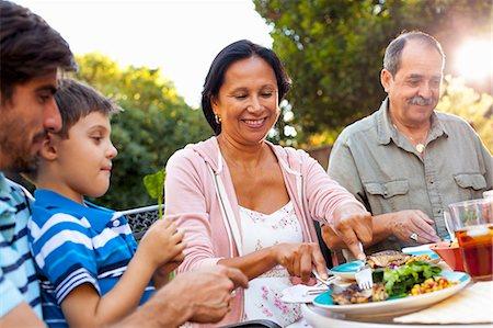 Three generation family dining in garden Stock Photo - Premium Royalty-Free, Code: 614-08000163