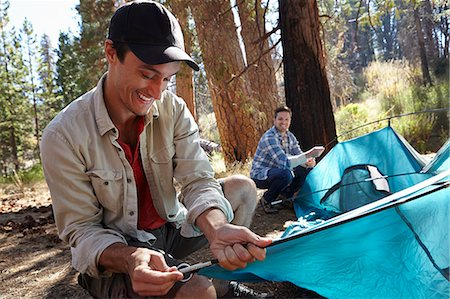 Two young male campers putting up tent in forest, Los Angeles, California, USA Stock Photo - Premium Royalty-Free, Code: 614-08000200