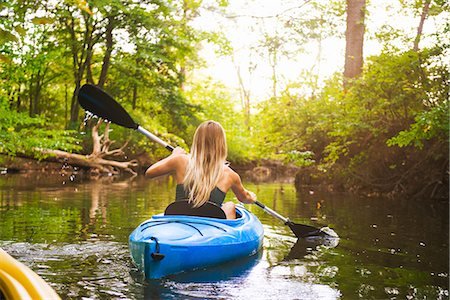 Rear view of young woman kayaking on forest river, Cary, North Carolina, USA Stock Photo - Premium Royalty-Free, Code: 614-08000222