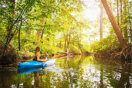 Young woman kayaking on forest river, Cary, North Carolina, USA Stock Photo - Premium Royalty-Free, Code: 614-08000223