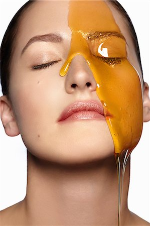 Female model's face partially covered in honey Stock Photo - Premium Royalty-Free, Code: 614-08000316