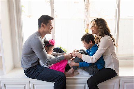 Mature couple and two children sitting on living room window seat Stock Photo - Premium Royalty-Free, Code: 614-08000342
