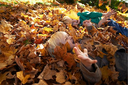 pile leaves playing - Two boys playing in pile of leaves Stock Photo - Premium Royalty-Free, Code: 614-08030436