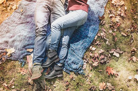 Overhead view of legs of couple lying on blanket in forest Stock Photo - Premium Royalty-Free, Code: 614-08030454
