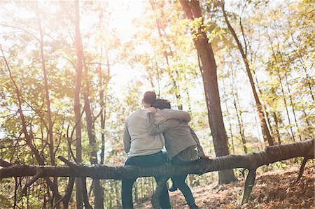 sweater - Rear view of couple sitting on fallen tree in forest Stock Photo - Premium Royalty-Free, Code: 614-08030460