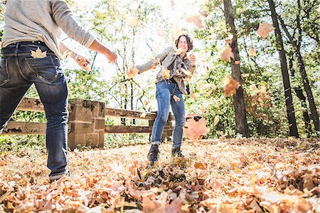 fall - Couple play fighting kicking autumn leaves in forest Stock Photo - Premium Royalty-Free, Code: 614-08030477