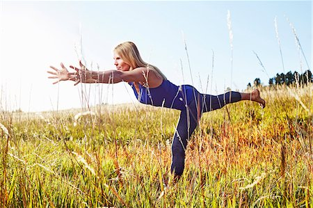 fitness   mature woman - Mature woman practising yoga on field Stock Photo - Premium Royalty-Free, Code: 614-08030504