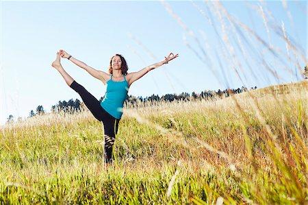 Mature woman practising yoga on field Stock Photo - Premium Royalty-Free, Code: 614-08030509
