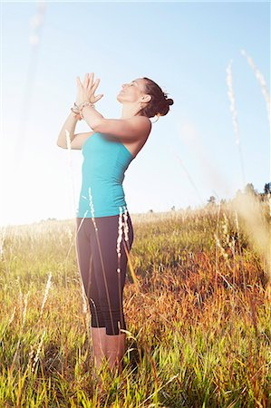 Mature woman practising yoga on field Stock Photo - Premium Royalty-Free, Code: 614-08030502