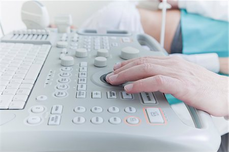 pregnant woman with doctor - Hand of sonographer using control panel whilst doing ultrasound scan Stock Photo - Premium Royalty-Free, Code: 614-08030611