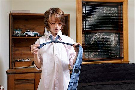 Boy practicing tying large tie in bedroom Stock Photo - Premium Royalty-Free, Code: 614-08030624