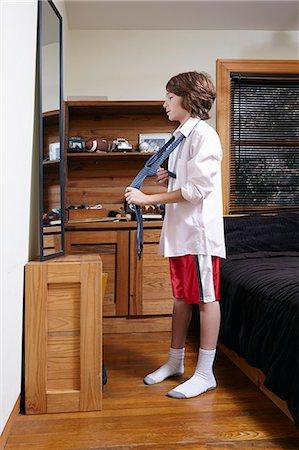 Boy practicing tying large tie in bedroom mirror Stock Photo - Premium Royalty-Free, Code: 614-08030625