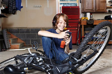 Boy in garage choosing music on smartphone Stock Photo - Premium Royalty-Free, Code: 614-08030627