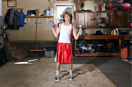 slim - Slim boy struggling to lift hand weights in garage Stock Photo - Premium Royalty-Free, Code: 614-08030628