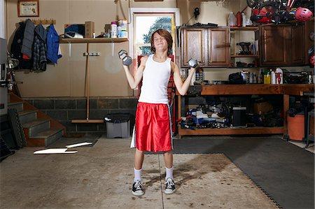 Slim boy struggling to lift hand weights in garage Stock Photo - Premium Royalty-Free, Code: 614-08030628