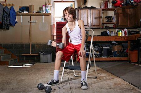 slim - Slim boy struggling to lift hand weight in garage Stock Photo - Premium Royalty-Free, Code: 614-08030629