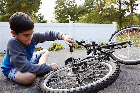 Determined boy repairing bicycle on driveway Stock Photo - Premium Royalty-Free, Code: 614-08030638