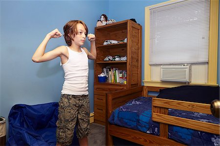 slim - Slim boy flexing arm muscles in bedroom Stock Photo - Premium Royalty-Free, Code: 614-08030631