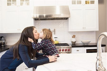 Mother kissing daughter in kitchen Stock Photo - Premium Royalty-Free, Code: 614-08030653