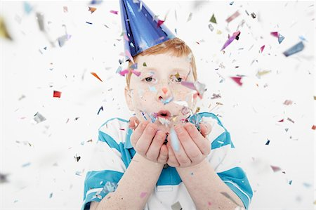 Boy wearing cone party hat blowing confetti Stock Photo - Premium Royalty-Free, Code: 614-08030840
