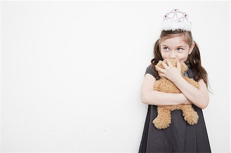 Girl wearing tiara holding teddy bear Stock Photo - Premium Royalty-Free, Code: 614-08030853