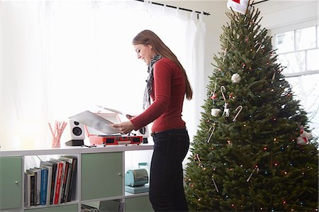 sweater - Young woman putting vinyl on record player at christmas Stock Photo - Premium Royalty-Free, Code: 614-08030887