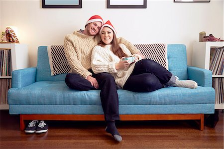 festive - Portrait of young couple in santa hats on sofa with christmas gift Stock Photo - Premium Royalty-Free, Code: 614-08030896