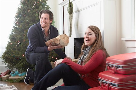 sweater and fireplace - Young couple preparing log fire at christmas Stock Photo - Premium Royalty-Free, Code: 614-08030890