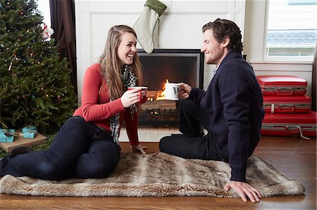 sweater - Young couple drinking coffee in front of log fire at christmas Stock Photo - Premium Royalty-Free, Code: 614-08030891