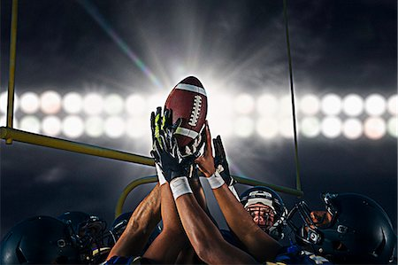 football team - Victorious teenage and young male american football team holding up ball at night Stock Photo - Premium Royalty-Free, Code: 614-08030966