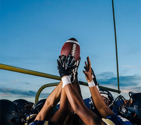 Victorious teenage and young male american football team holding up ball Stock Photo - Premium Royalty-Free, Code: 614-08030967
